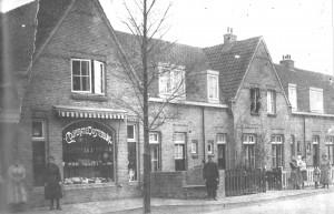 De tabakswinkel van 'Coöperatie Oostenburg' op de hoek van de De Lessepsstraat en de Galvanistraat. Toen de fotograaf langskwam om dit plaatje van de straat te maken, kwamen daar de bewoners even voor naar buiten.