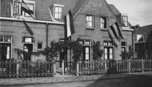 Prachtig versierde woning in de Marconistraat, ter gelegenheid van de thuiskomst van de Nederlands-Indië-ganger D. Mol. Van bijna iedere woning wappert een vlag. Boven de deur van nummer 20 (Hij staat open) hangt de tekst: Welkom Thu