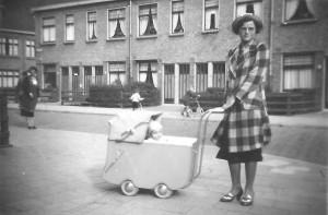 Mevrouw Jansen uit de Ampèrestraat staat in de Galvanistraat met een kinderwagen waarin haar neefje ligt.
