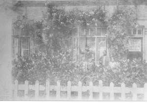Bij zo'n contrastarme foto moet je maar zo duidelijk mogelijk schrijven wat er hier in beeld gebracht is. Dit is het gezin Van Verseveld, dat in de voortuin van hun woning aan de Westinghousestraat nummer 44, op de foto ging. De vervaging doet vermoeden dat het om lang vervlogen tijden gaat en dat klopt wel, de foto is van 1927