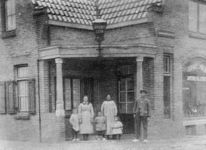 De familie Vossestein voor de winkel in de De Lessepsstraat 48. 'Handel in Melk boter kaas en eieren', maar de meerwaarde van de foto is het Brandsein aan de luifel.